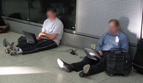 People Sitting on Floor to Get Access to Power Outlet.